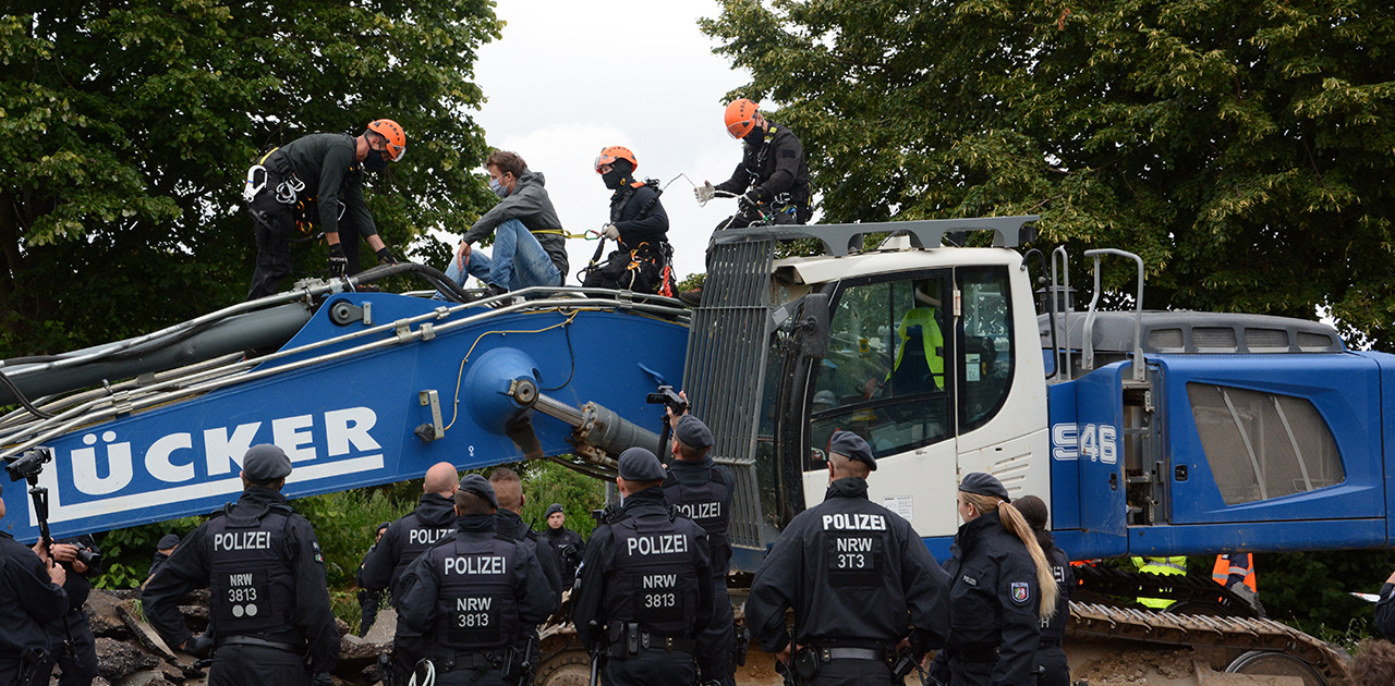 Eine Hundertschaft der Polizei rückte an, um die Landstraße im Kreis Heinsberg zu räumen – ein Aktivist war auf einen der Bagger geklettert