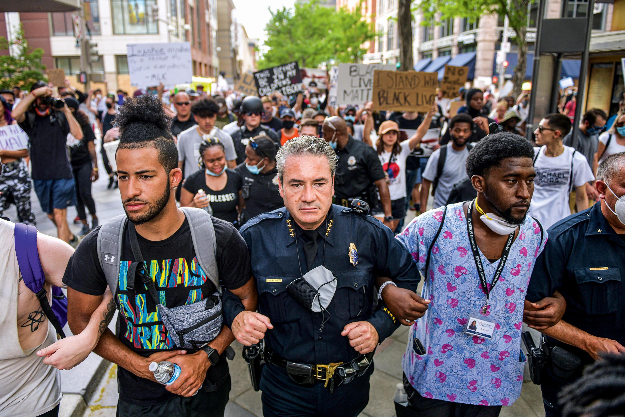 """ARM IN ARM Wenige Tage nach dem Tod von George Floyd, der im Polizeigewahrsam erstickte, solidarisieren sich Uniformierte aus Denver mit den """"Black Lives Matter""""-Demonstranten. Mittendrin: Polizeichef Paul Pazen"""