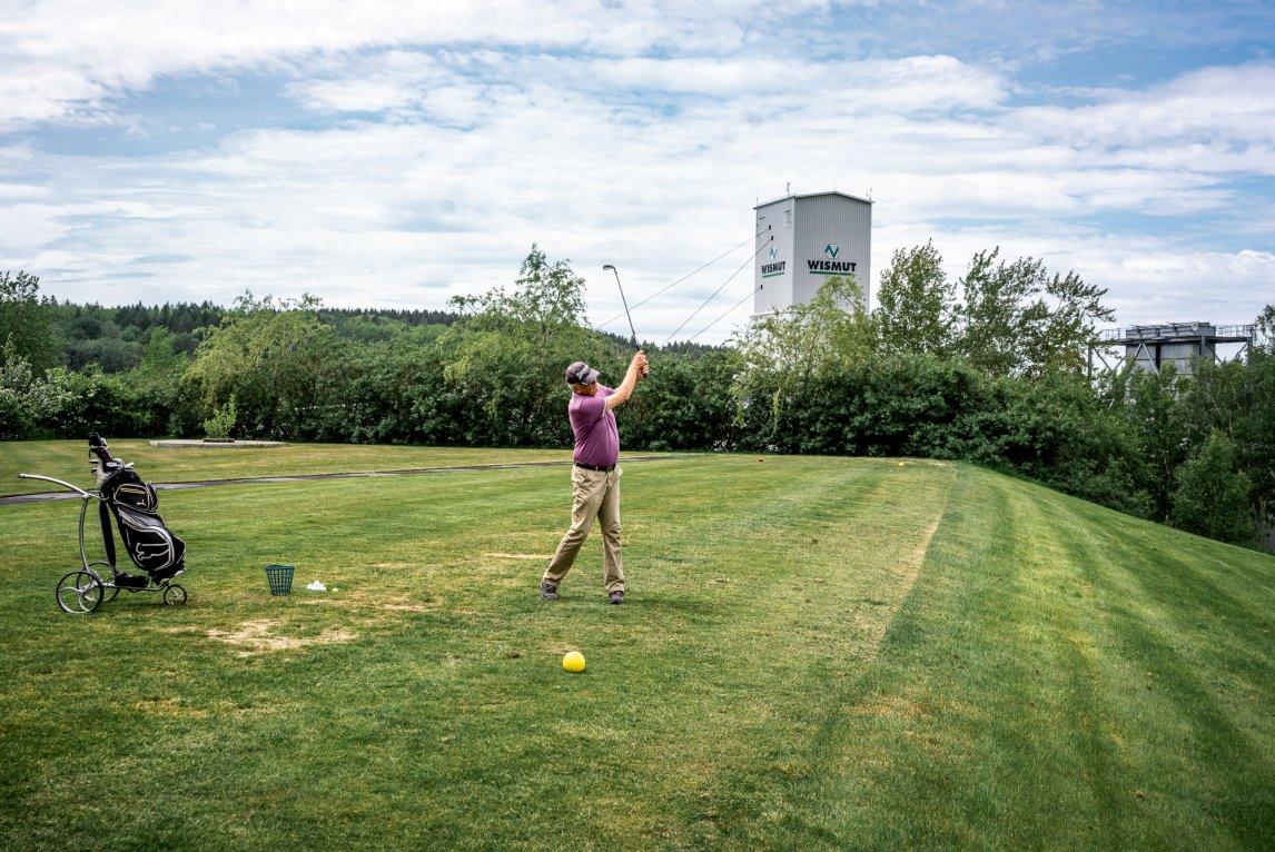 ÜBER TAGE Ein Besucher des Golfparks Westerzgebirge schlägt auf einer der ehemaligen Halden des Uranbergbaus ein paar Bälle in die Landschaft, hinter ihm der alte Wellblechturm des alten Staatsbetriebs