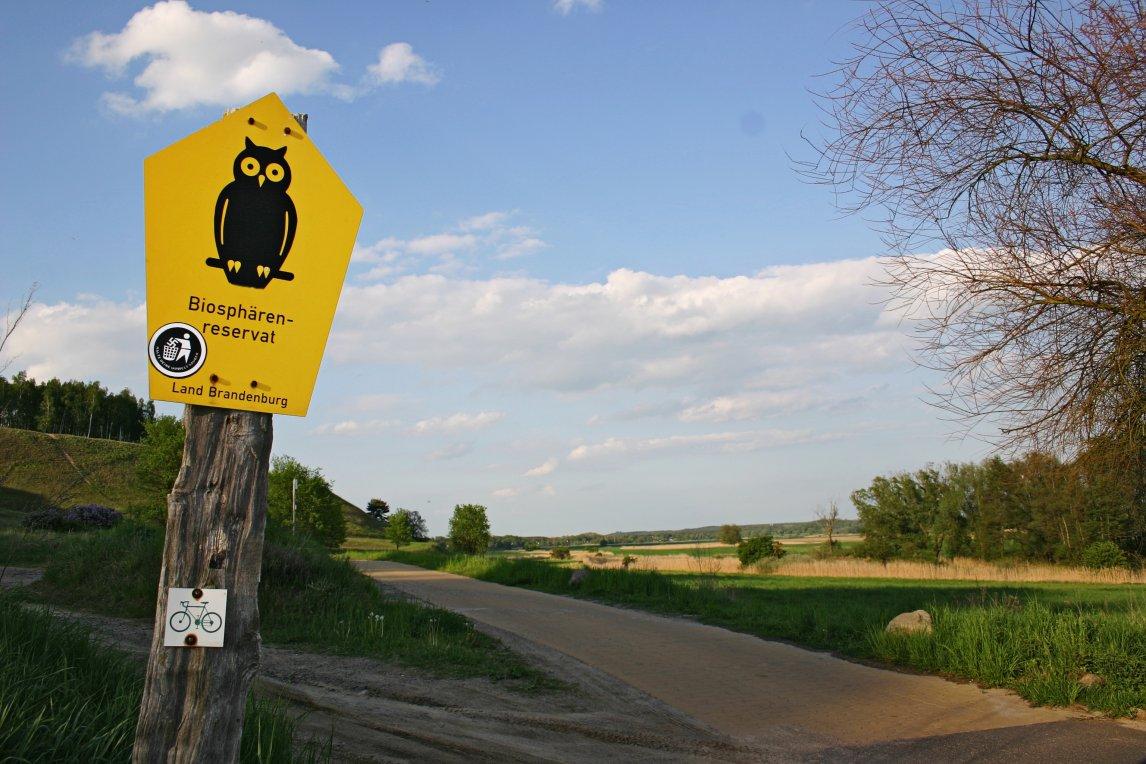 Eine Landschaft in Brandenburg. Auf dem Schild des Biosphären-Reservats klebt ein Anti-Nazi-Sticker